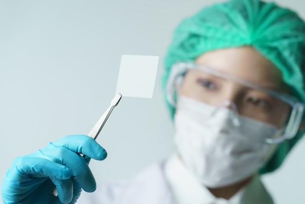 Doctor de las mujeres que sostiene el portaobjetos de cristal del microscopio vacío en el laboratorio.
