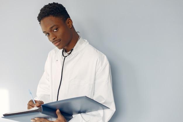 Doctor negro en un uniforme blanco con un estetoscopio