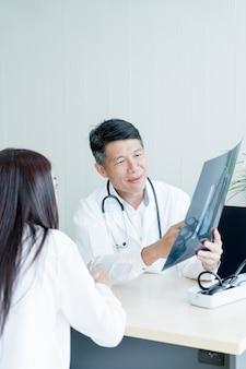 El doctor y el paciente asiáticos están discutiendo
