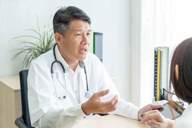 El doctor y el paciente mayores asiáticos están discutiendo
