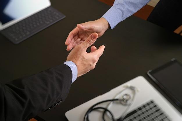 Doctor y paciente que sacuden las manos en oficina moderna en el hospital