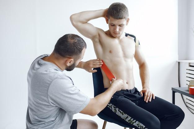 El doctor pega un tipi a un atleta en el hospital