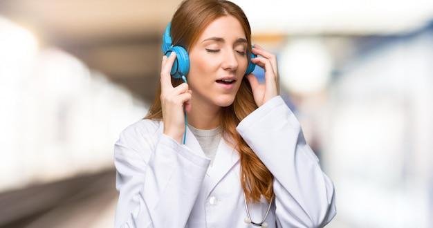 Doctor pelirrojo mujer escuchando música con auriculares en el hospital