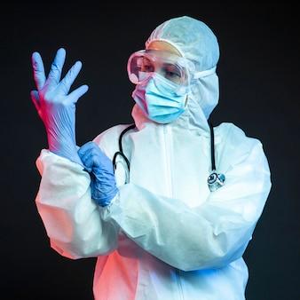 Doctor con ponerse guantes quirúrgicos