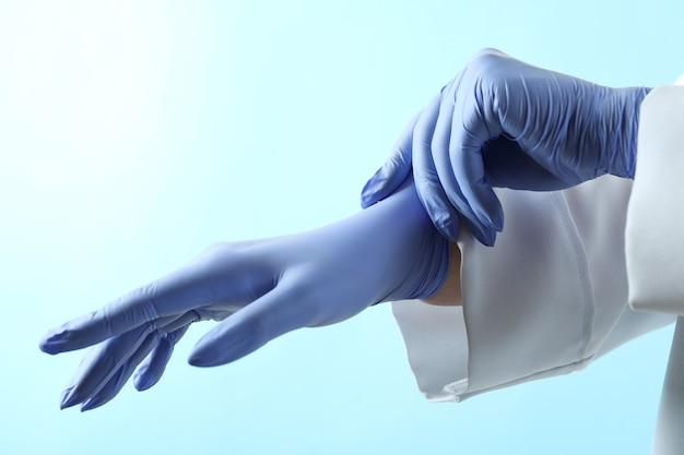 Doctor poniendo guantes médicos sobre fondo azul aislado