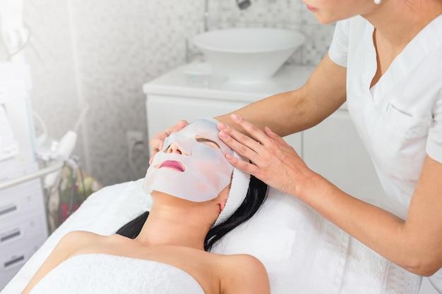 Doctor poniendo una mascarilla facial en el rostro de una mujer