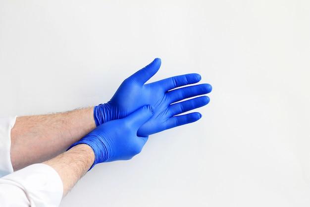Doctor poniéndose guantes protectores azules.