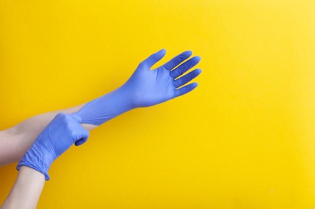 Doctor poniéndose a mano guantes médicos profesionales de nitrilo púrpura