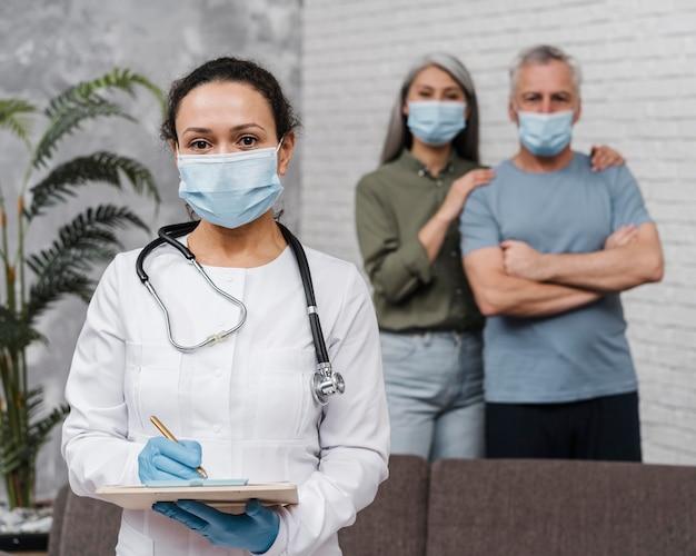 Doctor posando con sus pacientes detrás