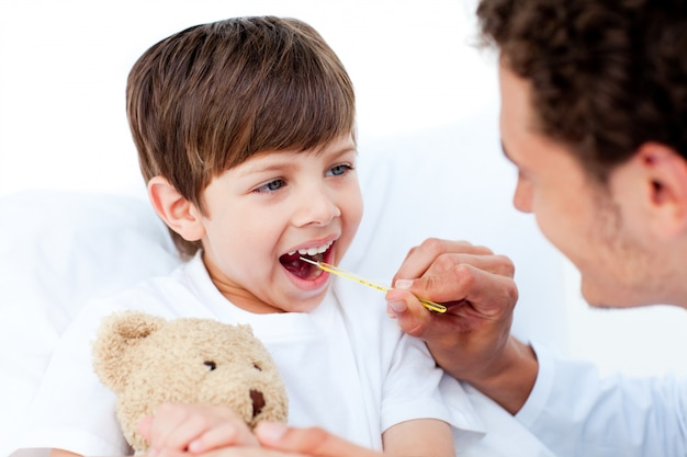 Doctor positivo tomando temperatura de niños pequeños