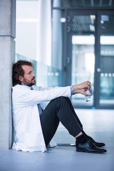 Doctor preocupado sentado en el piso