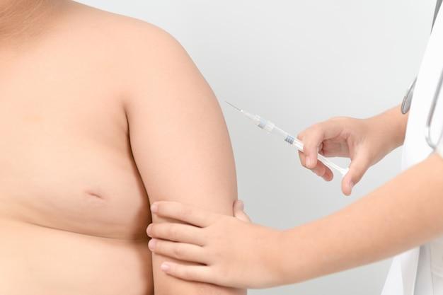 El doctor prepara la vacuna inyectable en el brazo del niño gordo obeso