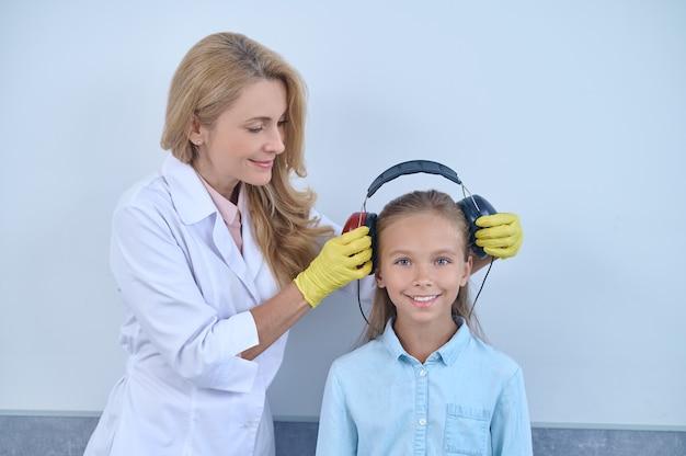 Doctor preparando a un paciente joven para una prueba audiométrica