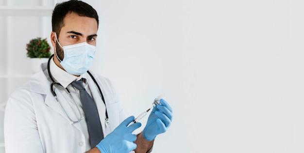 Doctor preparando una vacuna con espacio de copia