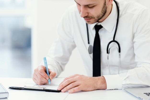 Doctor de primer plano escribiendo