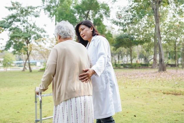 Doctor que ayuda a la mujer mayor asiática que usa al caminante mientras que camina en el parque.