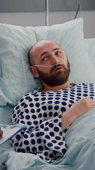 Doctor que controla al hombre enfermo escribiendo experiencia médica en el portapapeles mientras la enfermera pone el oxímetro para comprobar el pulso del corazón
