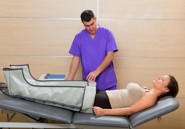 Doctor que controla la máquina de la presoterapia de las piernas en mujer