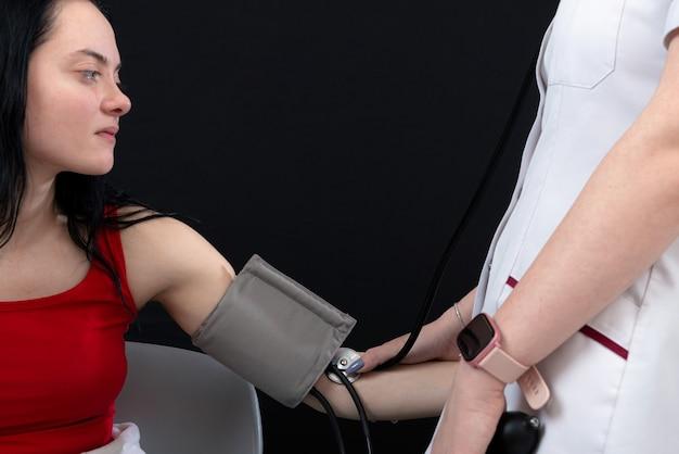 Doctor que controla la presión arterial del paciente, enfoque selectivo, primer plano, aislado en negro