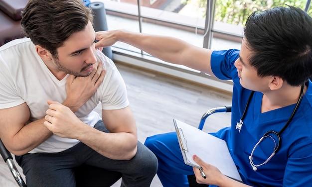 Doctor que examina el hombro herido del paciente joven del atleta en clínica