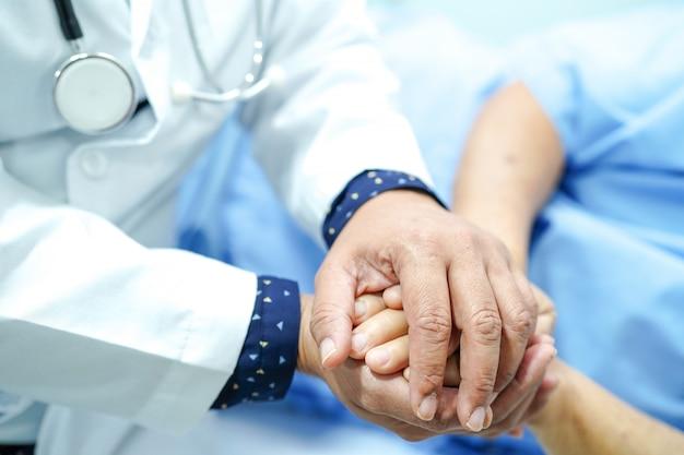 El doctor que lleva a cabo las manos asiáticas mayores ancianas mujer paciente con amor, cuidado y empaques