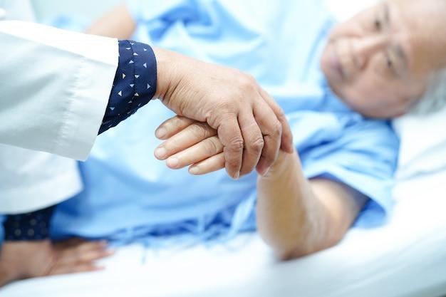 El doctor que lleva a cabo las manos asiáticas mayores o mayores ancianas mujer paciente con amor