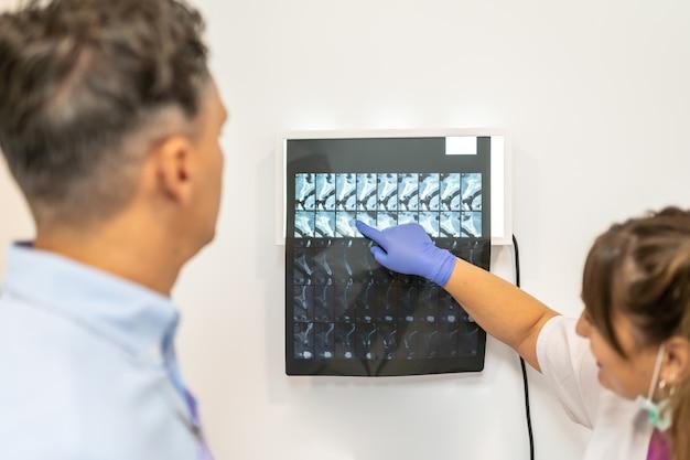 Doctor que muestra radiografía a su paciente.