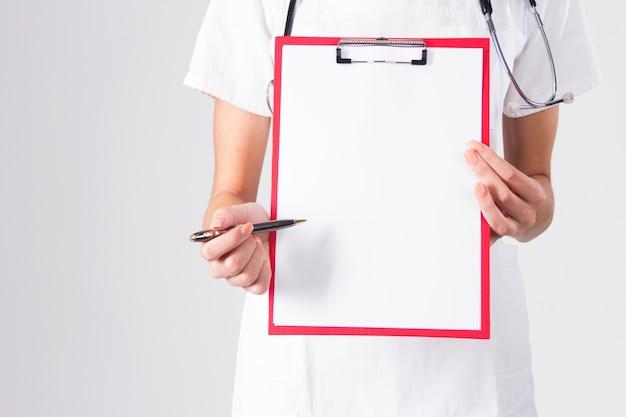 Doctor que muestra el sujetapapeles en blanco con la pluma aislada en un fondo blanco.