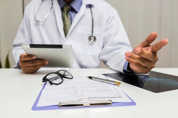 Un doctor que sostiene una tableta y consulta al paciente en oficina.