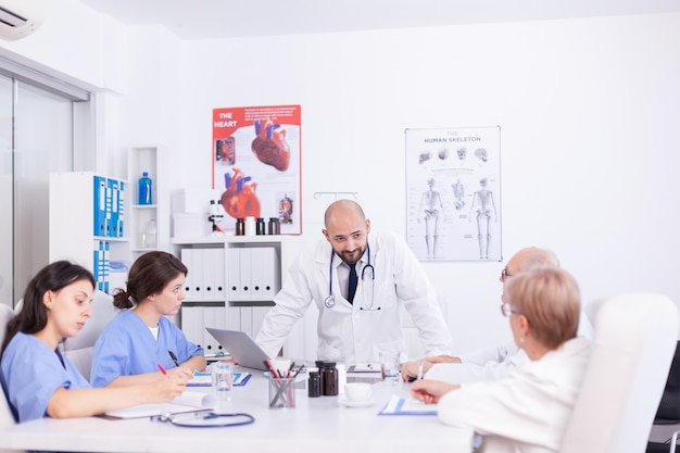 Doctor que tiene una discusión profesional con el personal médico en la sala de reuniones del hospital. terapeuta experto de la clínica hablando con colegas sobre la enfermedad, profesional de la medicina