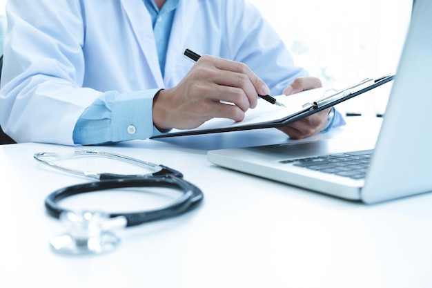 Doctor que trabaja con la computadora portátil y que escribe en papeleo. fondo del hospital.