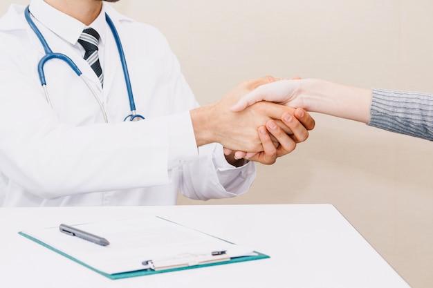 Doctor que tranquiliza a su paciente femenino con cuidado en la tabla de los médicos en hospital.healthcare y medicina