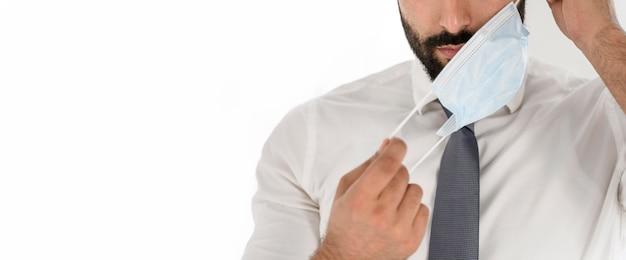 Doctor quitándose la máscara médica con espacio de copia
