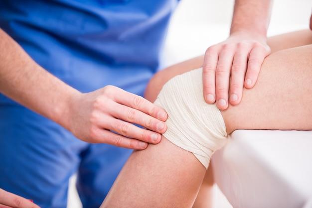 El doctor está rebobinando el vendaje de la rodilla a la mujer joven.