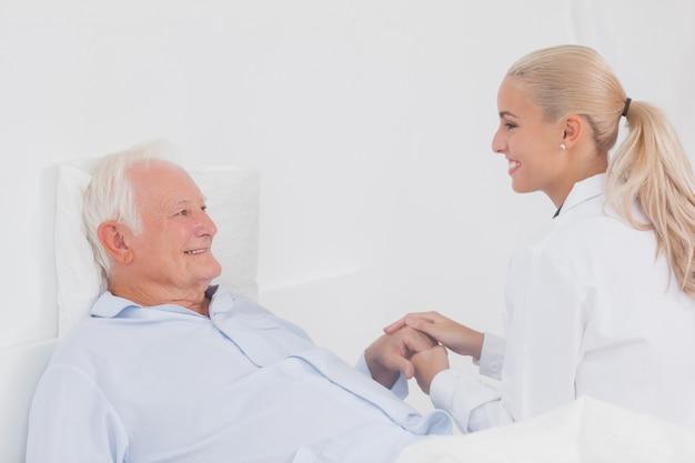 Doctor reconfortante paciente anciano