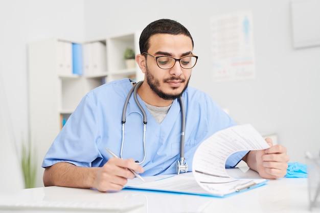 Doctor rellenando documentos