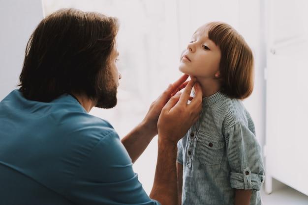 Doctor revisa cuidadosamente los nódulos linfáticos de los niños