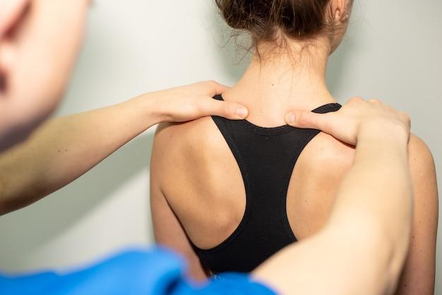 Doctor revisando la columna vertebral de una mujer joven dentro del examen médico anual