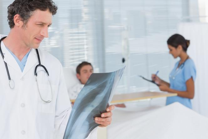 Doctor revisando la radiografía de pacientes en la habitación del hospital