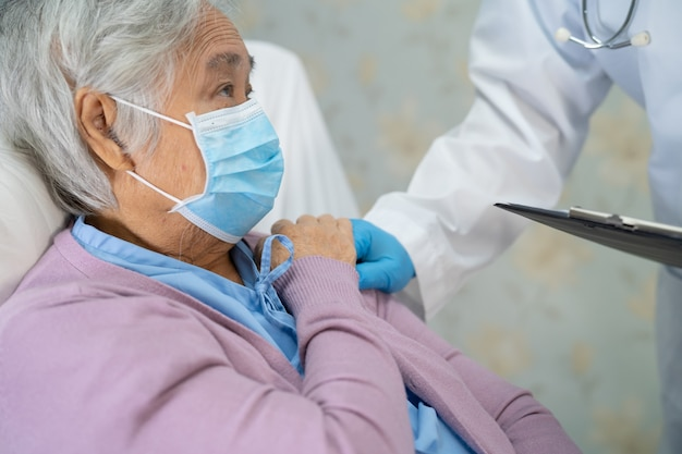 Doctor revisando a una paciente asiática mayor que usa una mascarilla para proteger el coronavirus covid-19.