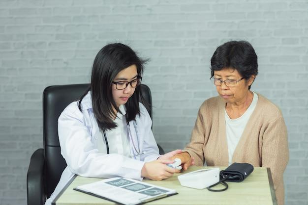 Doctor revisando presión anciana en gris