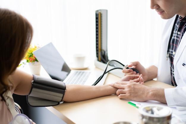 Doctor revisando la presión arterial de su paciente. concepto de cuidado y bienestar saludable.