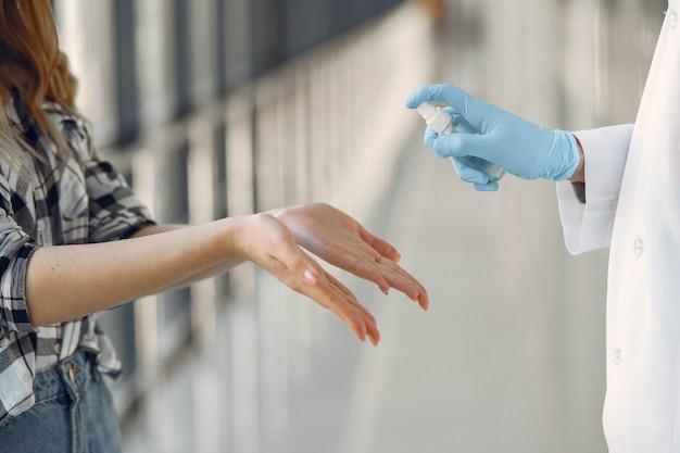 El doctor rocía el antiséptico en las manos del paciente.