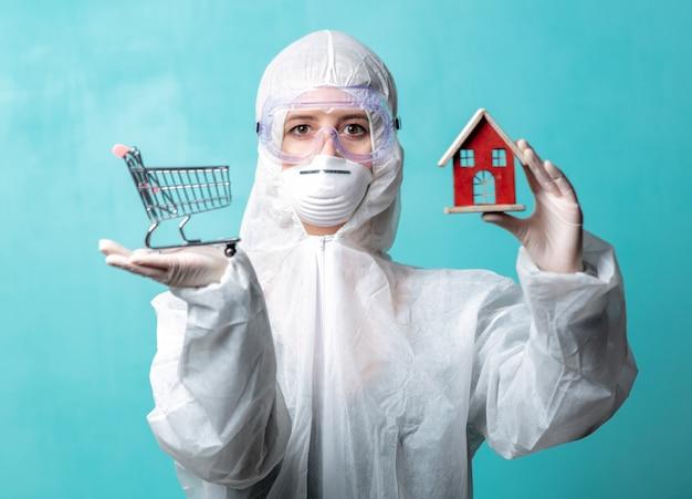 Doctor en ropa protectora sostiene un carrito de compras y una casa de juguetes, pidiendo quedarse en casa