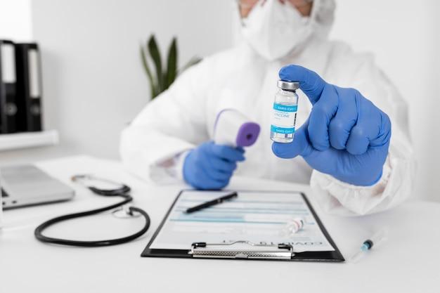 Doctor con rostro mak sosteniendo la vacuna covid
