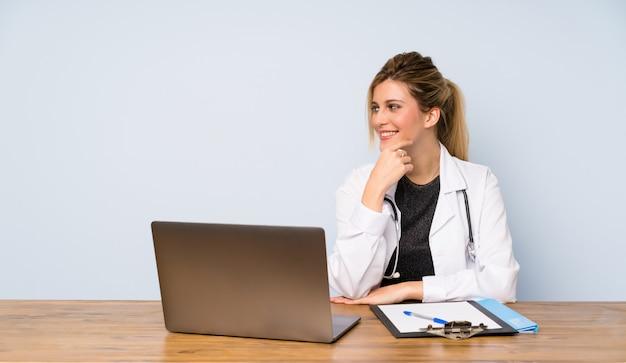 Doctor rubia mujer mirando hacia el lado
