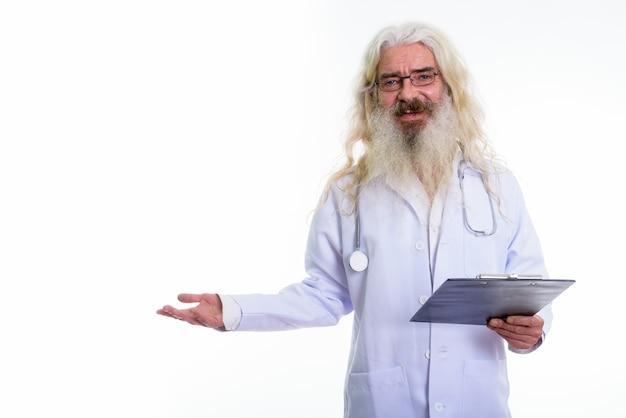 Doctor senior hombre barbudo pensando mientras sostiene un portapapeles