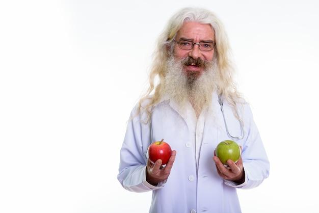 Doctor senior hombre barbudo sosteniendo manzana roja y manzana verde