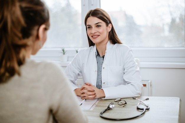 El doctor de sexo femenino hermoso en la capa médica blanca está consultando a su paciente.