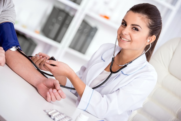 El doctor de sexo femenino joven hermoso está controlando la sangre.